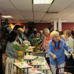 Staff serves seniors at tropical buffet.