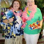 Friends in grass skirts and leis smile at tropical theme party.