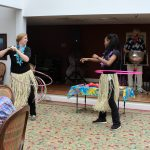 Staff members hula hoop event with Steel Pan music.